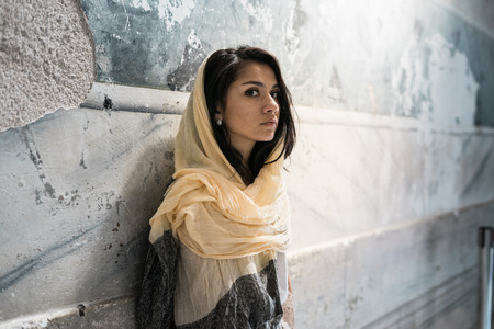 Portrait of a thoughtful sad girl in a headscarf on the head of the light sitting in the temple, praying Stock Photo - 88299670