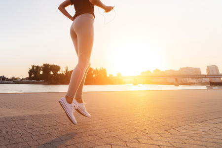young sporty girl runs by the river at sunset, listens to music on headphones