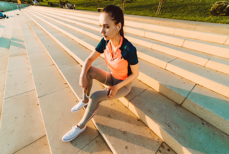 young athletic girl resting on the stairs after jogging, listening to music on headphones Stock Photo
