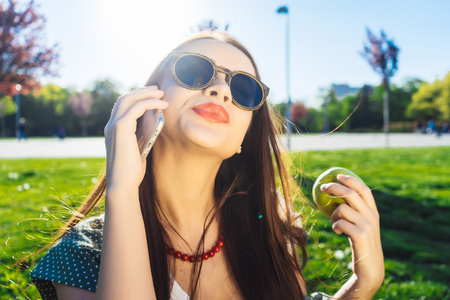 Pretty woman with mobile phone,outdoor.Girl in glasses Stock Photo