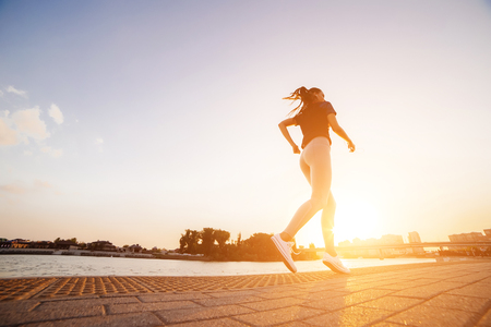 the girl is on a run at sunset. woman in the sportive clothes on the embankment of the river Stock Photo