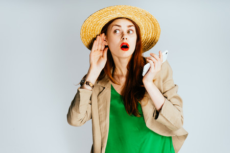 a funny girl in a green blouse and a big hat is holding a mobile phone and listening to extraneous sounds
