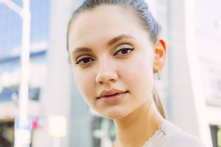 cute girl on a city street looking directly at the camera, close-up face Stock Photo