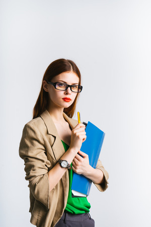 the red-haired girl with glasses and red lips is holding a folder with papers,  and looking at the camera. isolated Stock Photo