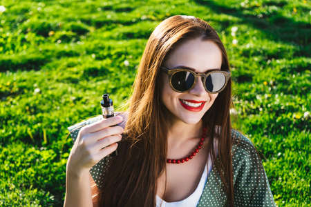 Happy fashion smiling Woman in sunglasses smoking vape on street,smoke Stock Photo