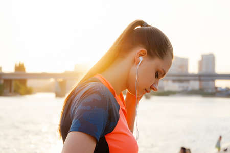 young beautiful sporty girl running near the river at sunset, listening to music on headphones Stock Photo