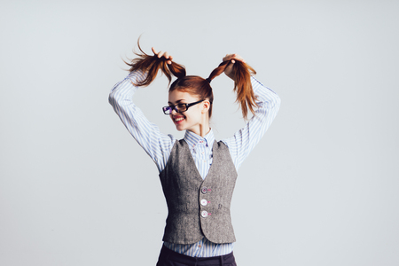 crazy girl in glasses keeps her tails, isolated on white background