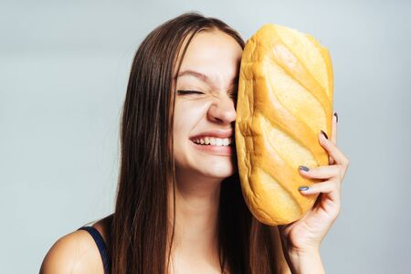young sporty smiling girl watching his figure, holding in his hands harmful white bread Stock Photo