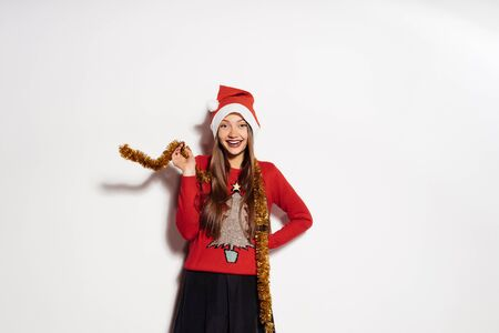tinsel: a young beautiful happy girl celebrates New Year and Christmas, wearing a red cap and a trendy warm sweater, with a golden tinsel around her neck Stock Photo