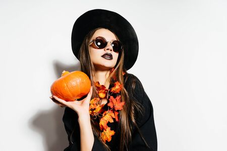 a young sexy gothic girl celebrates halloween, dressed in a witch, in a large black hat decorated with yellow autumn leaves, holds a pumpkin