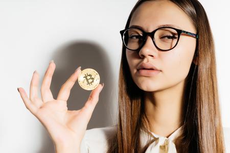 メガネの若い現代成功した女の子彼女の手で黄金 bicoin を保持しています。