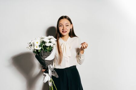 young beautiful girl holding a large bouquet of white flowers and sneezes because she is allergic