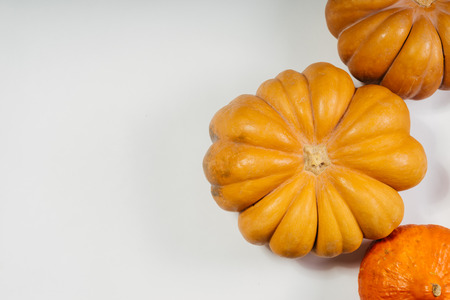 composition for decorating a house for halloween, on a white table lie orange and yellow pumpkins Stock Photo