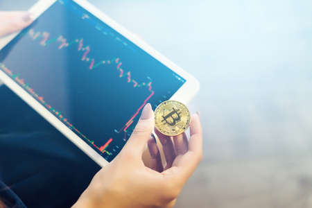 modern successful girl holds a gold bitcoin and a tablet with charts of crypto currency Stock Photo