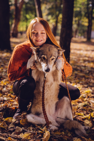 play the old park: happy girl hugging her dog in the autumn park Stock Photo