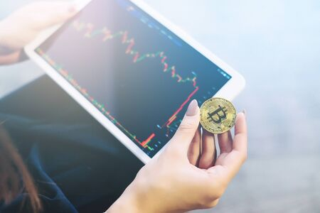 technology transaction: girl with a tablet in her hands closely follows the bitcoin course Stock Photo