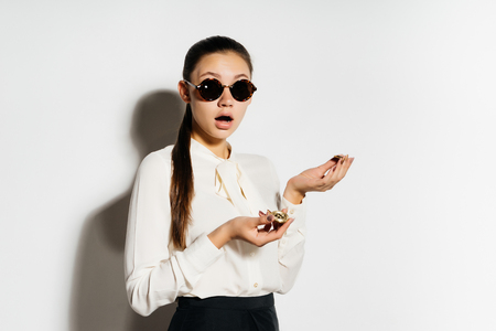 surprised girl in black glasses holds a pair of coins in hands Stock Photo
