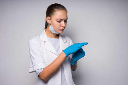 girl doctor in white medical gown removes blue silicone gloves Stock Photo