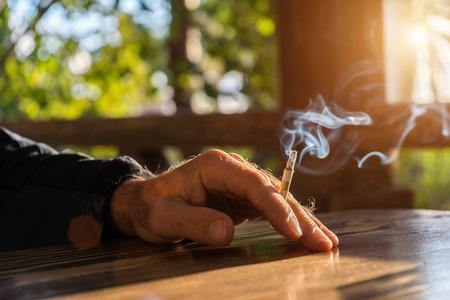 テーブルの上にある太陽の光線にたばこを保持している、大人の男の手