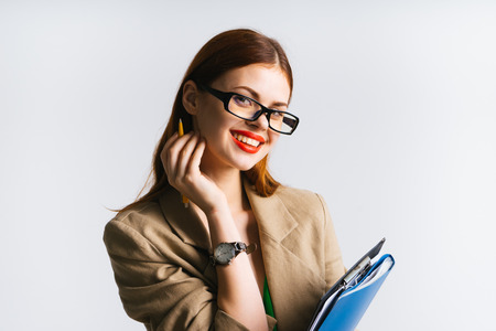 young beautiful girl in glasses and with red lipstick holds a folder with documents in her hands and smiles