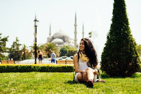 A bright Turkish girl sits on the grass on the background of the Blue Mosque in Istanbul