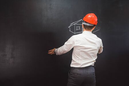 man builder in a white shirt and an orange protective helmet draws a house with chalk on a blackboard Banque d'images