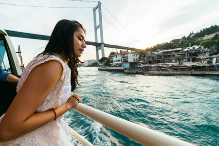 Curious young girl looks at the city in surprise, boat trip on the Bosphorus, modern bridge