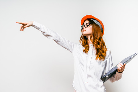red-haired girl builder wearing glasses and a safety helmet holding documents in her hands and pointing her finger to the side