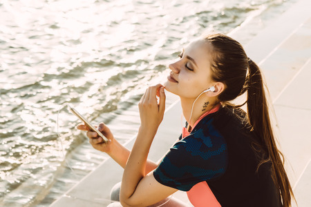 young sporty girl with long hair resting after jogging by the river, listening to music on headphones