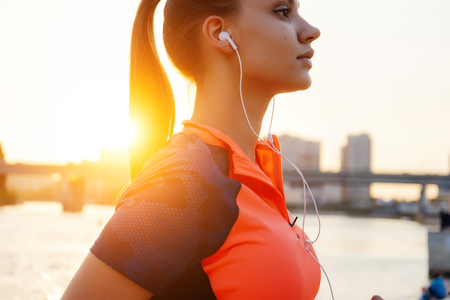 beautiful sports girl engaged in fitness at the river, at sunset, listening to music on headphones Stock Photo