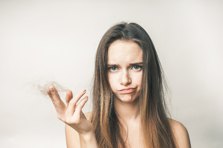 sad young girl with long hair holds a clump of her hair in her hand Stock Photo