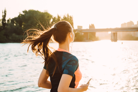 young sporty girl with long hair jogging by the river at sunset, listening to music on headphones