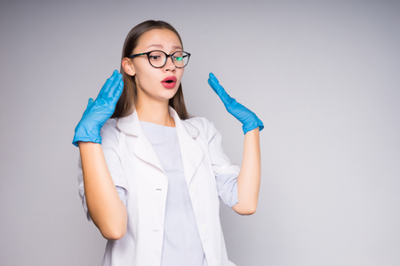young successful woman doctor wearing glasses and gloves looks surprised