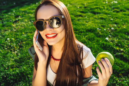 Happy smiling woman in sunglasses use cell phone and holds apple Stock Photo