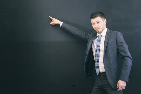 young successful confident man in suit shows his finger on chalk board