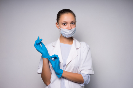 cute young woman doctor in protective medical mask puts on gloves