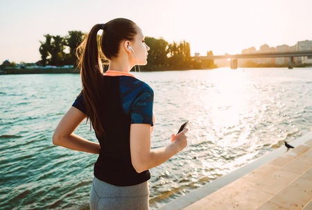sports girl is running at the river at sunset
