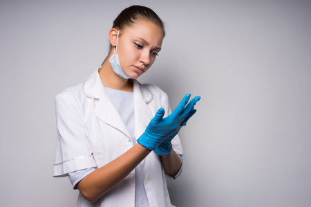 a pensive young girl in a white medical gown puts on blue silicone gloves Stock Photo