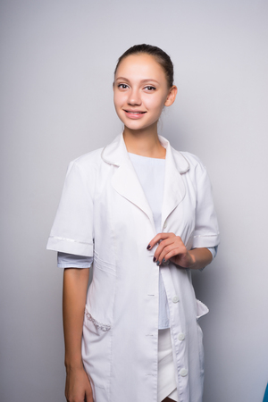 young cute girl in white medical dressing gown smiling, looking at camera