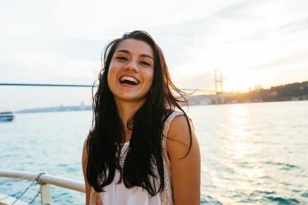 어린 소녀 여행자 일몰, 바다, 다리 배경에 찾고 요트에 순항하는 동안 이완. 이스탄불의 도시 보스포러스 해협 스톡 콘텐츠