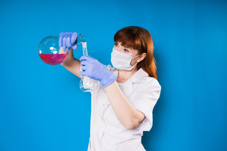 girl in a white robe holds a flask of reagents in her hands.the woman in the mask makes an experience Stock Photo