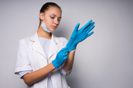 A sad girl in a white coat and wearing a mask puts on gloves. Isolated on white background Stock Photo