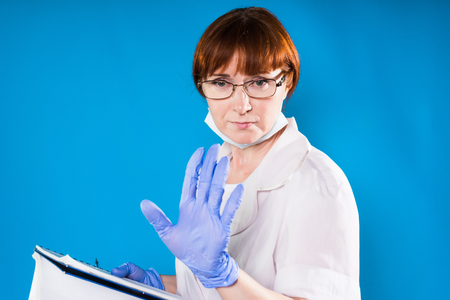 a woman in medical uniform and with glasses seridito shows a stop hand and holds a folder in her hand, isolated on a blue background Stockfoto