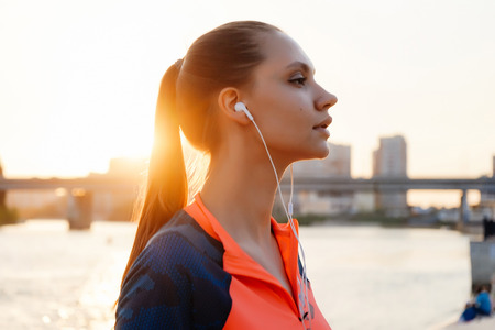 beautiful sporty girl runs by the river at sunset, listening to music on headphones Stock Photo