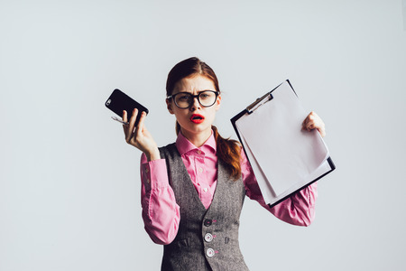 telephone interview: stylish angry girl with glasses, with red lipstick holds a smartphone and documents in her hands, Stock Photo