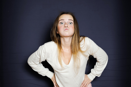 funny young girl in a white sweatshirt puffed out her cheeks, behind a black background