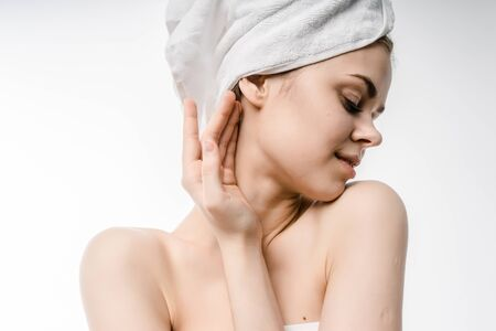beautiful young girl with clean skin, with a white towel on her head posing