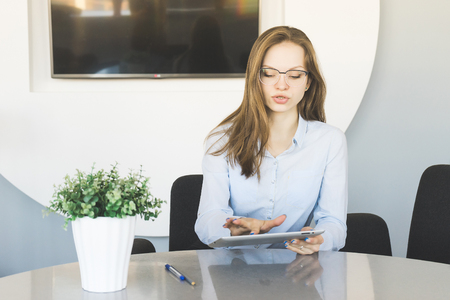 stylish successful girl in glasses and blue shirt is working in the office, looking at the tablet Stock Photo