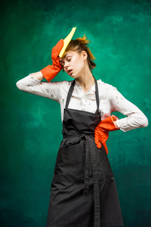 a young girl in a black protective apron, rubber gloves wipes sweat from her forehead because she is tired