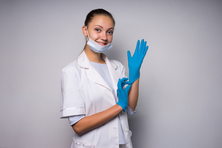 young smiling doctor girl in white medical dressing gown puts on blue gloves, looks at camera Stock Photo